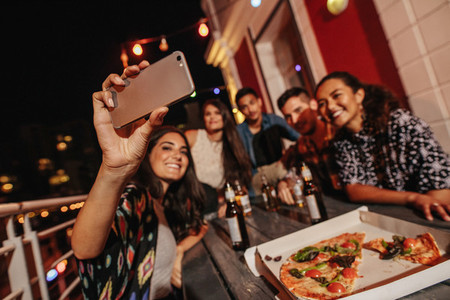 Group of friends making a selfie at rooftop party