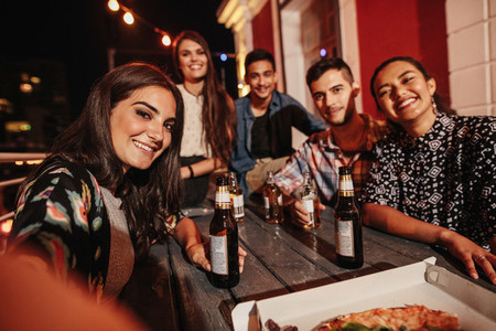 Woman taking selfie with friends at rooftop party