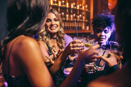 Group of friends having drinks at night club