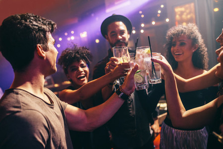 Group of friends at nightclub celebrating with drinks
