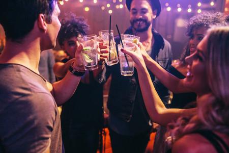 Friends at nightclub celebrating with drinks