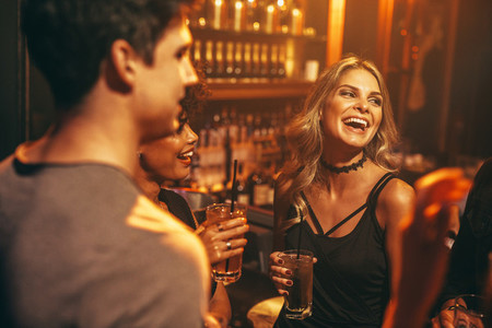Young woman having drink at nightclub with friends