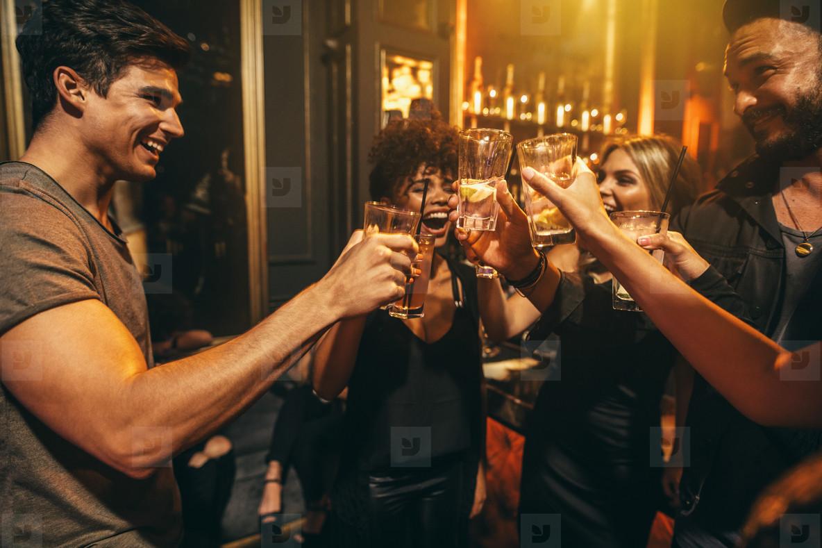 Group of men and women enjoying drinks at nightclub