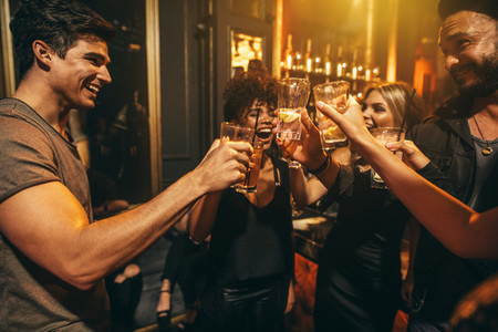 Group of men and women enjoying drinks at nightclub