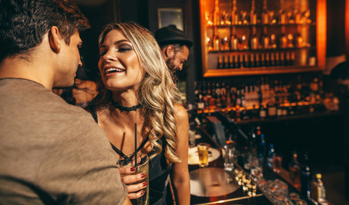 Young man and woman having good time at nightclub