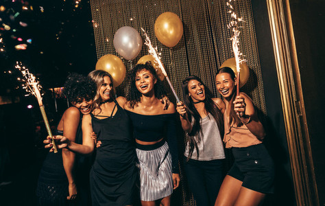 Group of women celebrating with fireworks at pub
