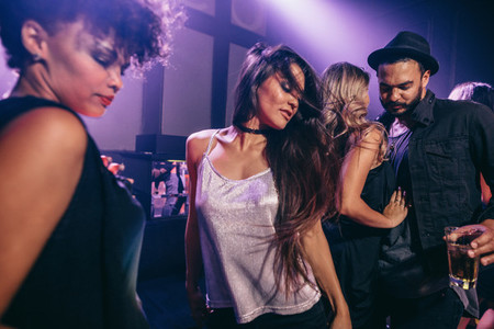 Woman dancing at party with friends at nightclub