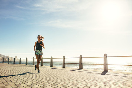 Healthy woman running on the sea side promenade