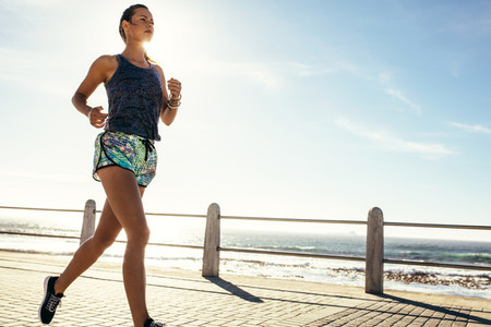 Female runner running along the road by the sea