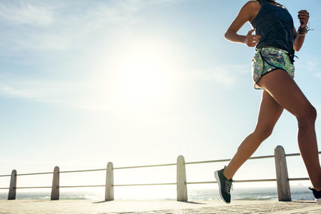 Fitness woman running on ocean front