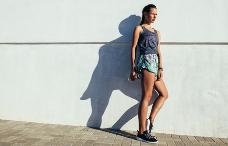 Fitness woman leaning to a wall and looking away