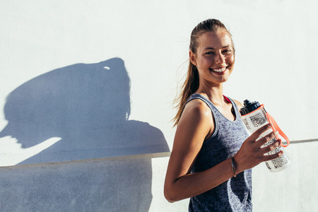Happy female runner holding water bottle and smiling