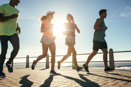 Group of runners running on road by the seaside