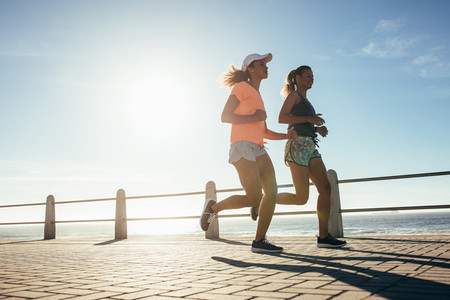 Two young women running on ocean front