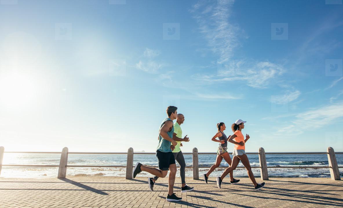 Group running along a seaside promenade
