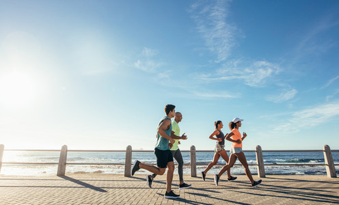 Group running along a seaside promenade