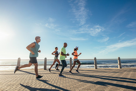 Group of athletes running on ocean front
