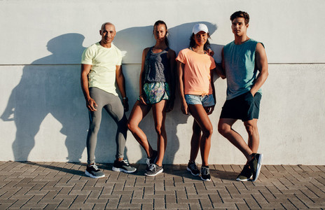 Young runners standing together by a wall