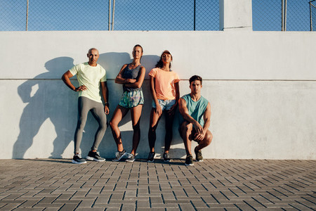 Diverse fitness group posing by a wall