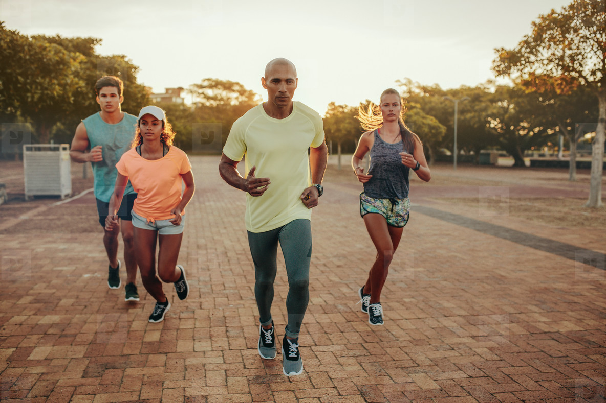 Fit young man runs with friends
