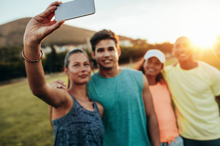 Woman taking selfie with friends at park