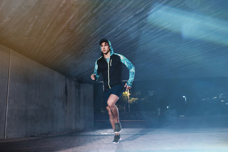 Fit young man jogging in the city at night