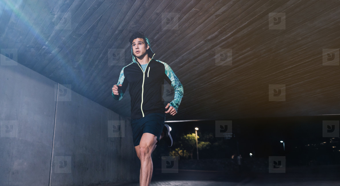 Young man jogging at night in city