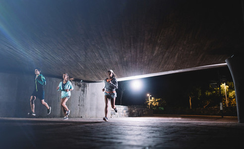 Group of runners training in the city at night