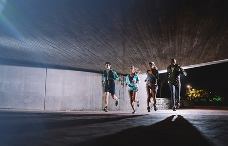 Group of young people running together at night