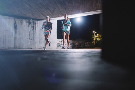 Young women jogging under bridge at night