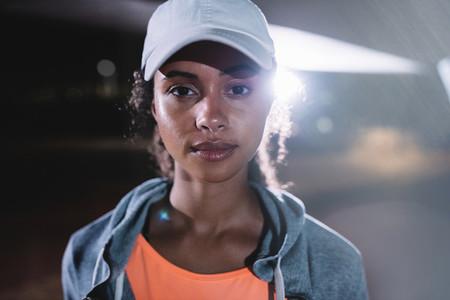 Urban female runner in city at night