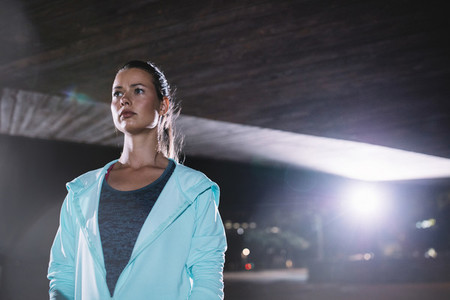 Female runner standing under bridge at night