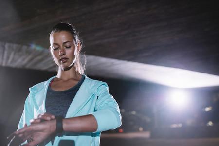 Urban runner checking fitness progress on smartwatch