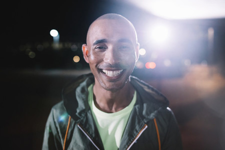 Smiling runner standing in city at night