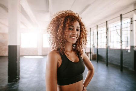 Smiling young fitness model in health club