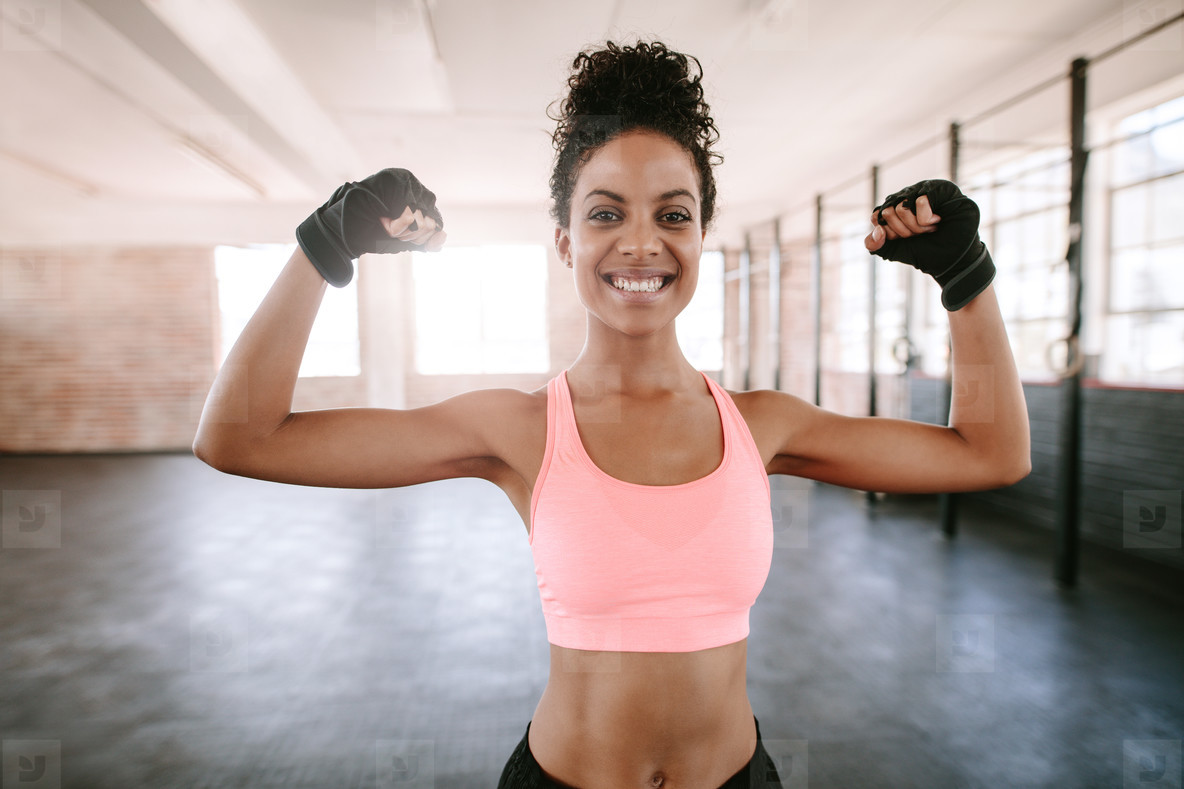 Fitness woman flexing muscles