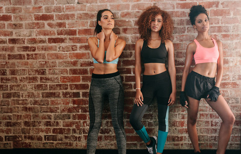 Three fitness women standing against brick wall