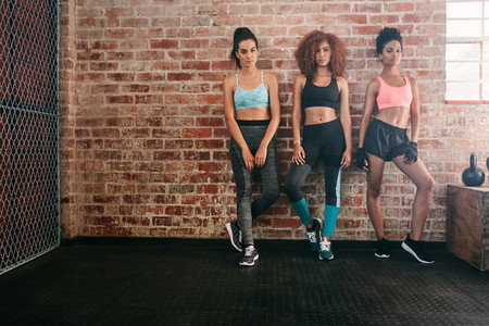 Fitness women standing together in gym