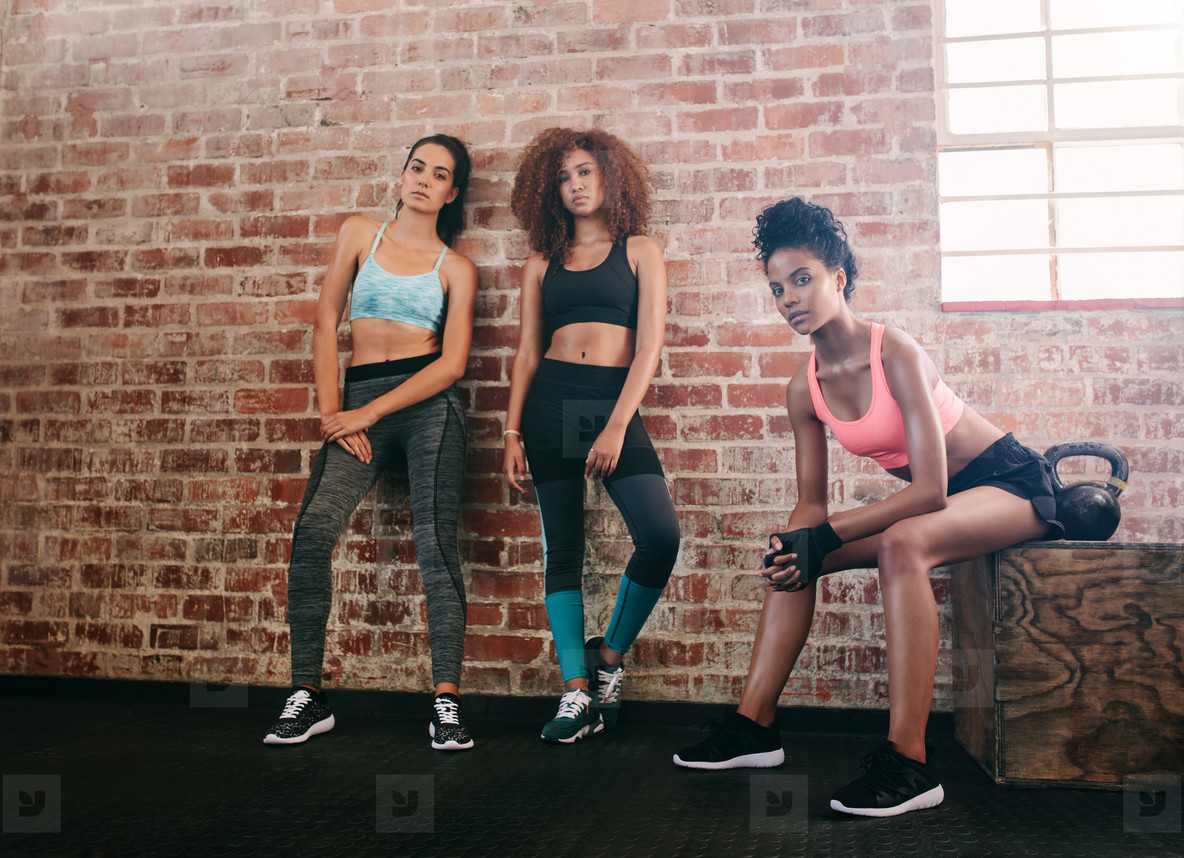 Young women resting after workout in gym