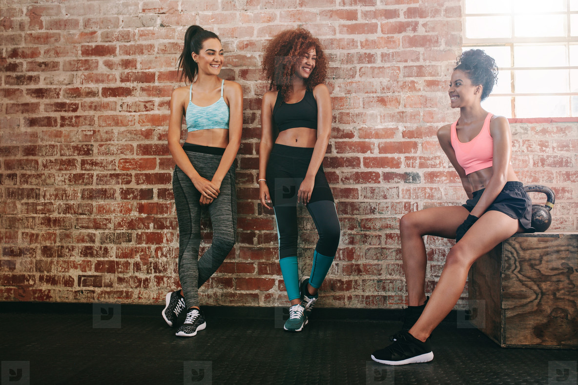 Three mixed race women relaxing in gym