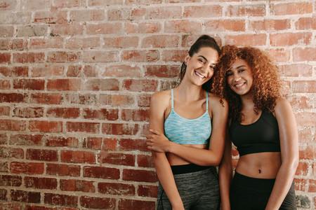 Two happy young women in sportswear
