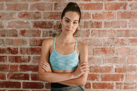 Beautiful young woman in sportswear against brick