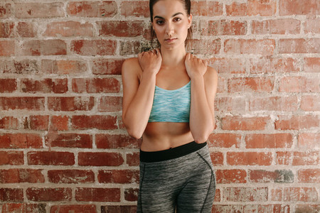 Beautiful woman in sportswear posing against brick wall