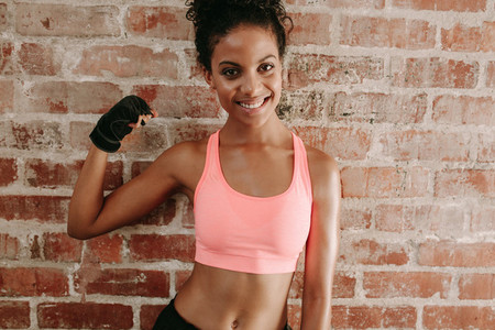 Young fitness woman flexing muscles and smiling