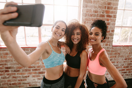 Happy young girls in sportswear taking selfie in gym