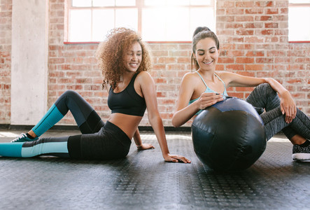 Two young female friends in gym with medicine ball