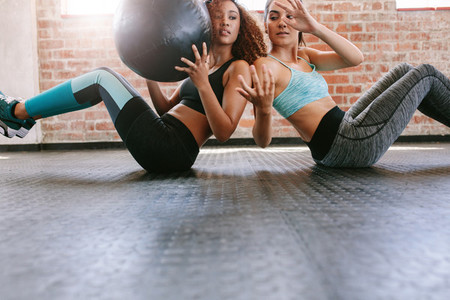 Girls working out in gym with medicine ball