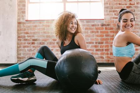 Female friends taking a break from workout in gym
