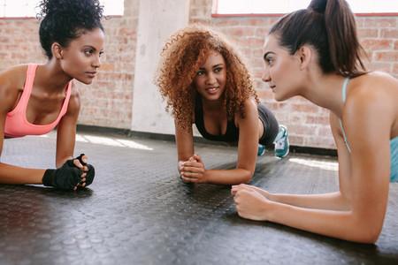 Three young women doing pushups