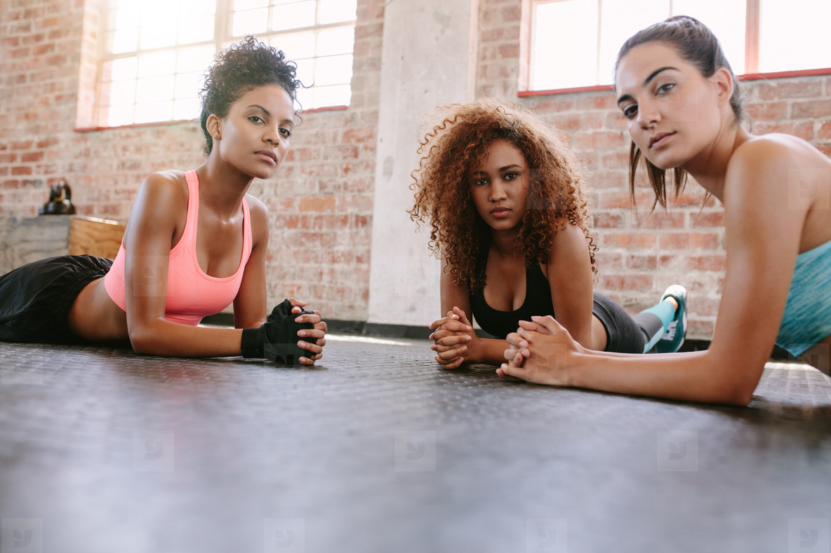 Three young women lying on gym floor